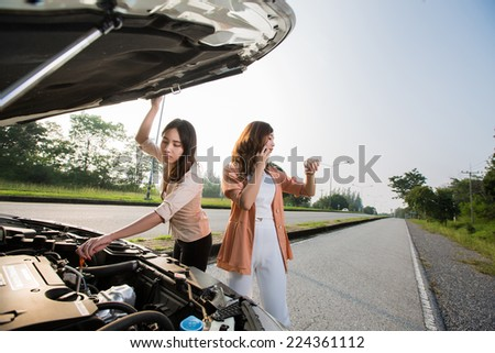Asian woman broken car on the road is a phone and watch. Tell a car mechanic - stock photo