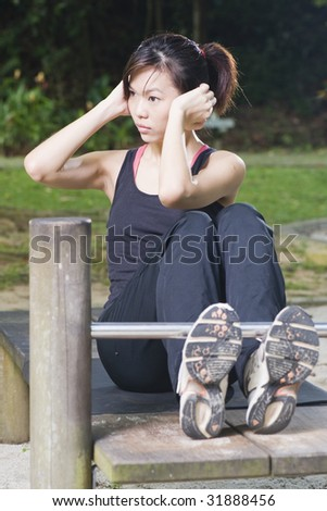 asian woman doing sit ups at a fitness corner - stock photo
