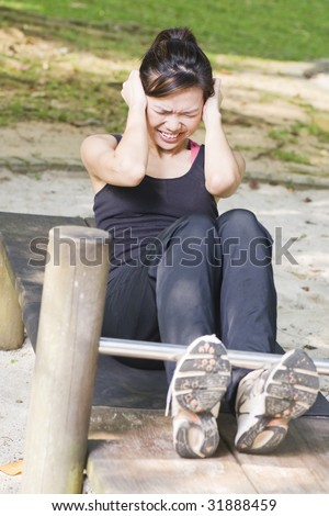 asian woman doing sit ups at a fitness corner but struggling at it