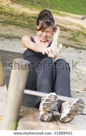 asian woman doing sit ups at a fitness corner but struggling at it - stock photo
