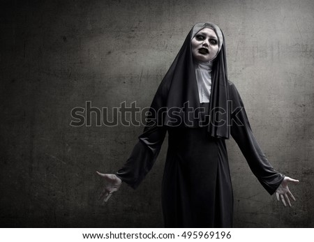 Asian woman dressed in evil nun standing in front of wall