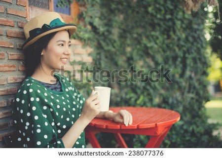 Asian woman drinking coffee outside , Vintage color - stock photo