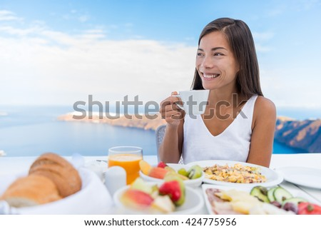 Asian Woman drinking hot drink at morning Breakfast table. Beautiful elegant lady having coffee cup on luxury hotel terrace with sea view at resort restaurant on Oia Santorini island, Greece. - stock photo
