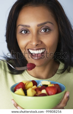 Asian woman eating fruit salad - stock photo