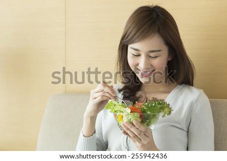 Asian woman eating healthy salad. - stock photo