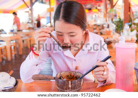 Asian woman eating noodle in the restaurant - stock photo
