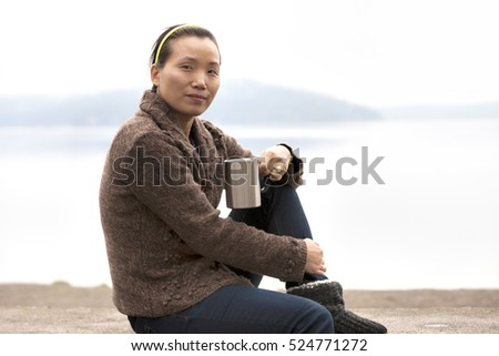 Asian woman enjoys coffee by lake.