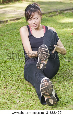 asian woman experiencing leg cramp after a physical activity