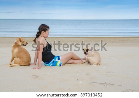Asian woman girl playing with two dog on beach, Pug and Labrador Retriever - stock photo