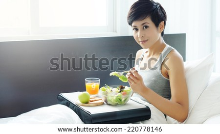Asian woman having light breakfast in bed - stock photo