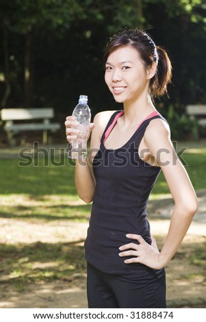 asian woman holding a bottle of water for hydration after exercise - stock photo