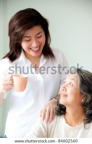 asian woman holding a cup looking senior woman - stock photo