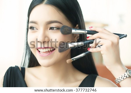 Asian woman holding brushes - beauty makeup concept - stock photo