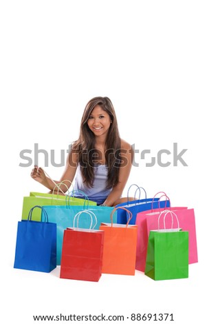 Asian woman holding receipt sitting with a bunch of colorful shopping bags - stock photo