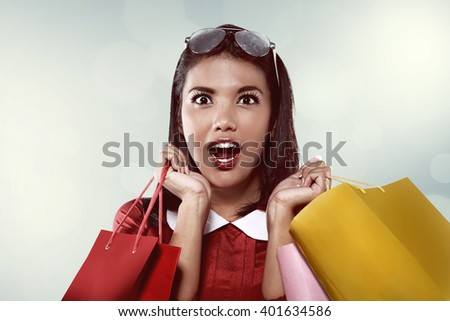 Asian woman holding shopping bag look happy