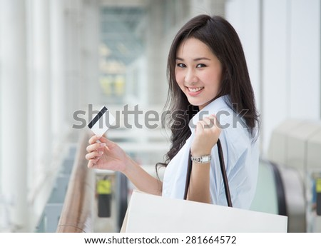 Asian woman holding shopping bags and a card