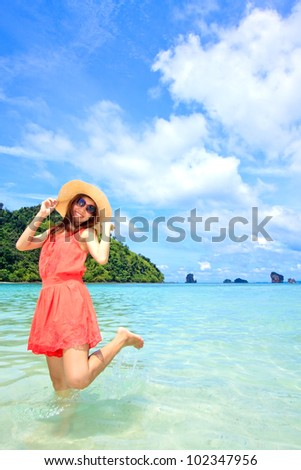 Asian woman in a pink dress standing on the beach - stock photo