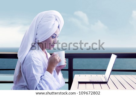 Asian woman in bathrobe holding cup of coffee and looking at laptop computer with ocean view - stock photo