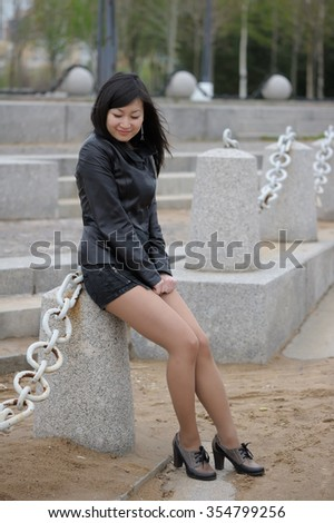 Asian woman in black jacket at park - stock photo