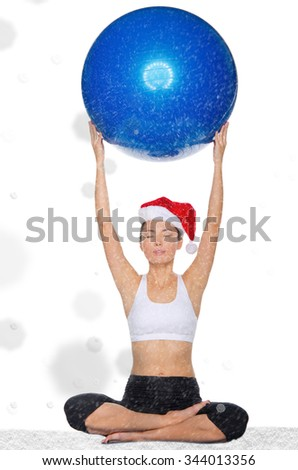 asian woman in christmas cap holds pilates ballsunder  snow isolated on white - stock photo