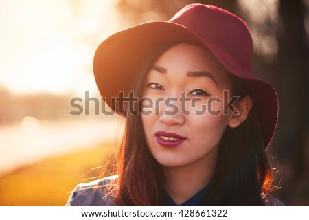 Asian woman in hat outdoors - stock photo