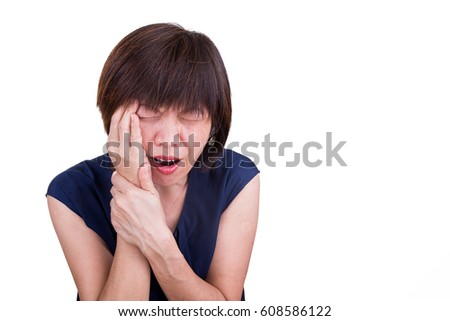 Asian woman in intense pain with hands over face on white background