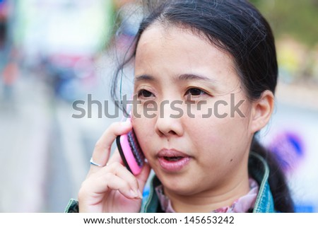 Asian woman in jeans jacket talking to phone