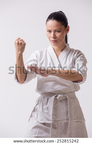 Asian woman in kimono show block in martial art exercise on white - stock photo