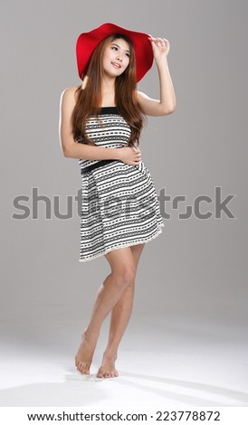 Asian woman in striped tube top and flare skirt set with red hat.