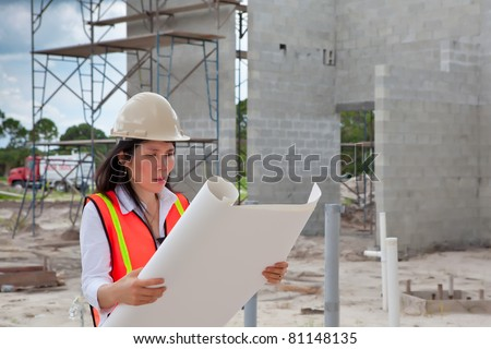 Asian Woman Inspector on construction site. Scaffolding, truck, plumbing pipes and  block walls in background. - stock photo
