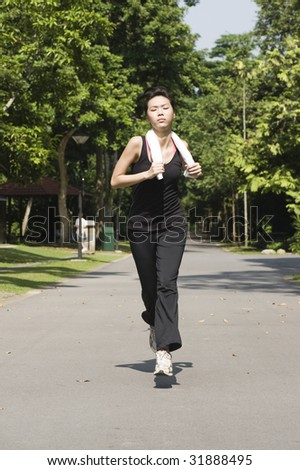 asian woman jogging alone outdoors in a park - stock photo