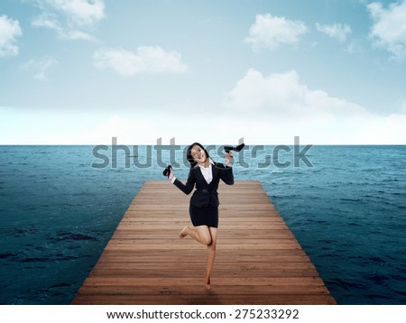 Asian woman jumping on the pier wearing business suit. Business travel concept
