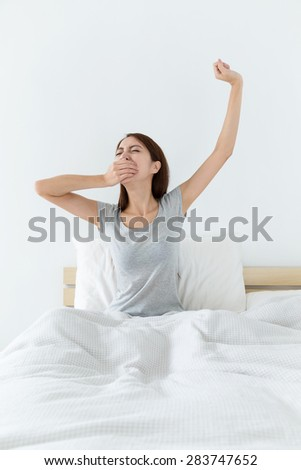 Asian woman just wake up , yawning and hand raised up - stock photo