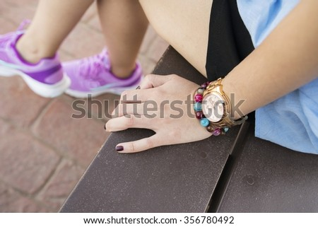 Asian Woman left hand with bracelet & Gold watch - Woman holding hand on wooden bench at public park - stock photo