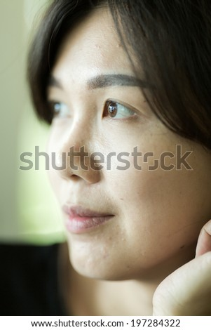 Asian woman look out of window - stock photo