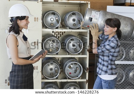 Asian woman looking at female industrial worker carrying propane cylinder - stock photo