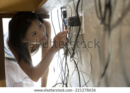 Asian woman looking at plugs under desk - stock photo