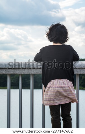 Asian woman looking at sky and lake