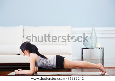 Asian woman on a yoga mat doing the dolphin plank pose.