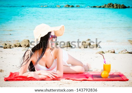 Asian woman on beach drinking cocktail - stock photo