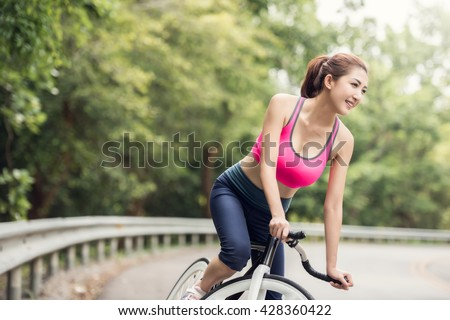 Asian Woman On Cycle Ride In Countryside