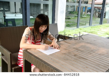 asian woman on desk with paper outdoor - stock photo