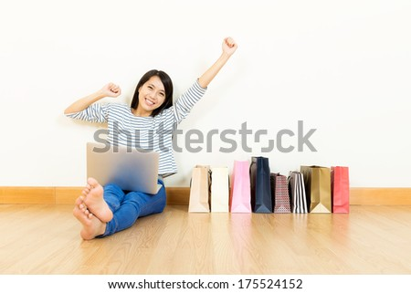 Asian woman online shopping at home with assorted paper bag - stock photo