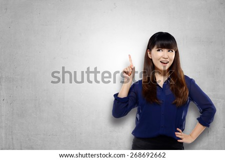 Asian woman point something over grunge background. You can put your message on empty space - stock photo