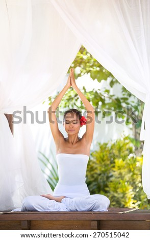 Asian woman practicing yoga in the morning with sun ray through the baldachin - stock photo