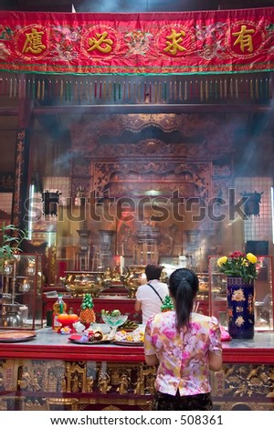Asian woman praying in a temple. - stock photo