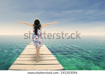 Asian woman raised her hands on beach deck symbolizing freedom - stock photo