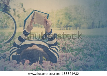 Asian woman reading booklet on the grass. Vintage style. - stock photo