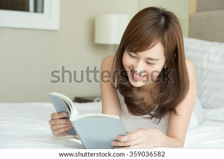 Asian woman reading in bedroom - stock photo