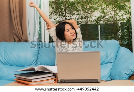 Asian woman relaxing and stretching arm after study in laptop computer - stock photo